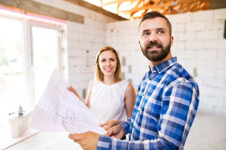 young-couple-at-the-construction-site-P6PHZ48.jpg